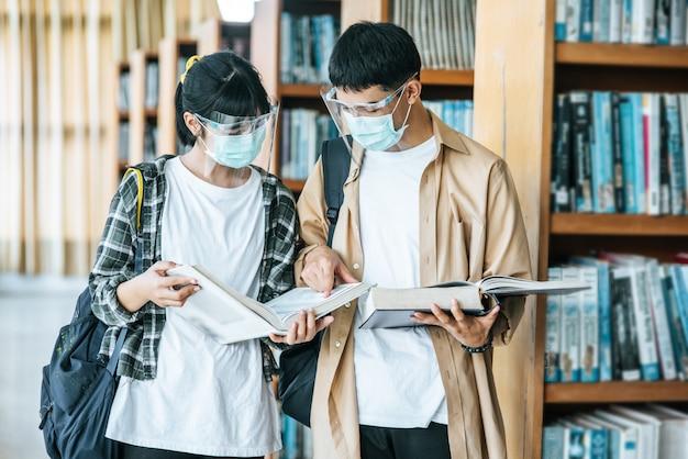 マスクをした男性と女性が立ち、図書館で読書をします。