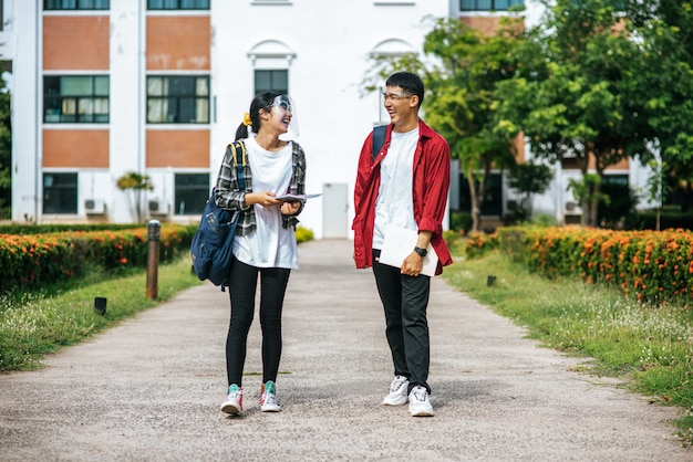 男性と女性の学生は顔を冷やし、大学の前に立っています。