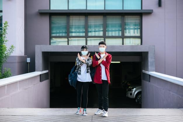 男性と女性の学生はマスクを着用し、大学の前に立っています。
