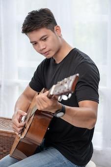 椅子に座ってギターを弾く男。