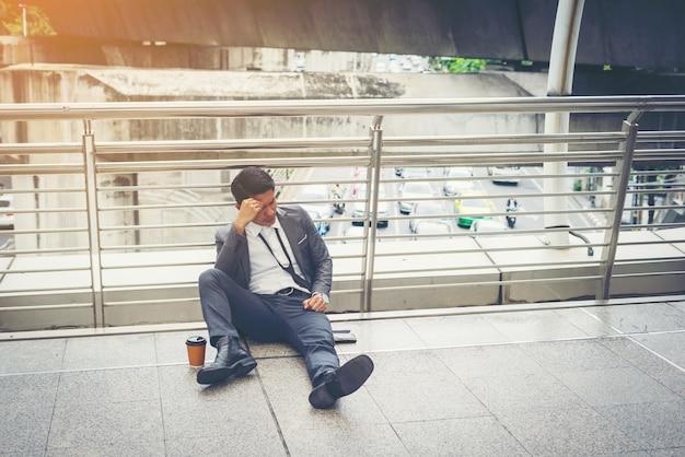 床に座っているビジネスマンが強調した。