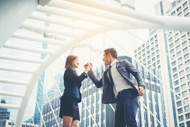 Бизнес пара руки вверх делать да на открытом воздухе. концепция совместной работы