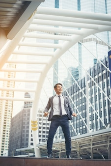 Портрет привлекательный бизнесмен празднует прыжки поднимает кулак над головой на улице.