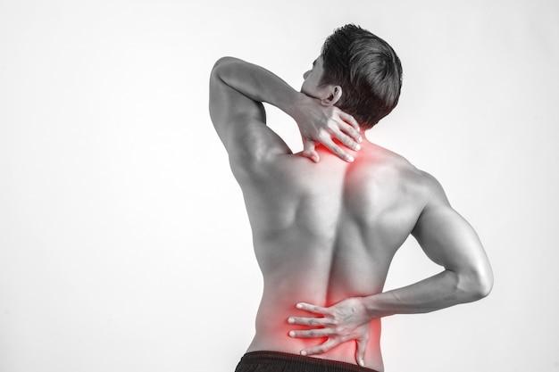 彼の痛みを伴う後ろをこすっている男の近くには、白い背景があります。