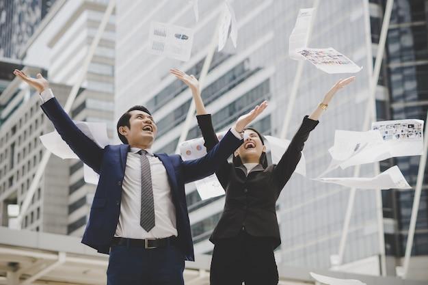 Деловые люди бросают бумаги, стоя перед офисным зданием. бизнес успешная концепция.