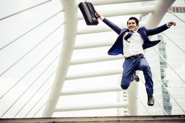 都市の通りを走っているブリーフケースを持つ若い実業家は、仕事に行くために急いでいます。