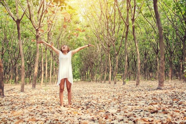 Счастливая девушка бросать сухие листья