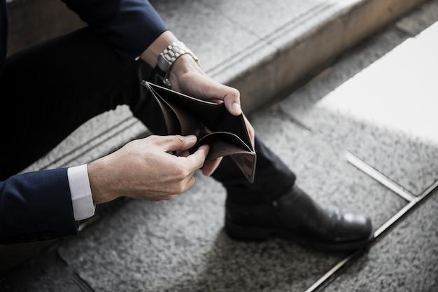 彼の手に空の財布を持っているビジネスマンのクローズアップ。