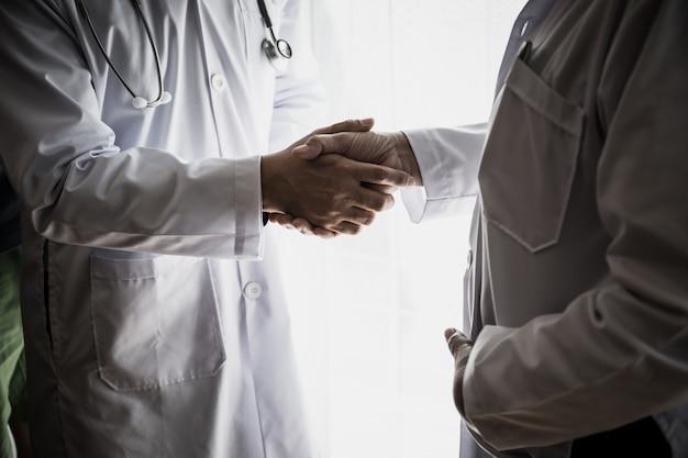 成功した彼のパートナーに握手をしている医師のクローズアップ。