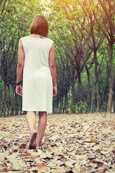 葉で覆われた地面の女の子の歩行の背面図