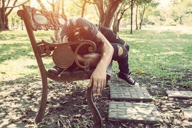 Усталый человек лежал на деревянной скамье