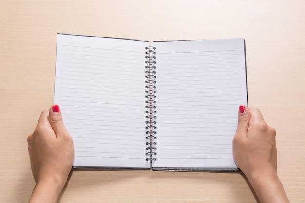 オープンノートブックを保持女