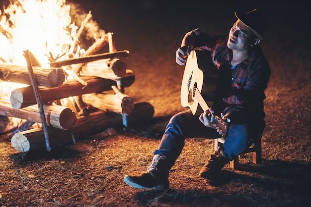 キャンプファイヤーの周りに座っているギター