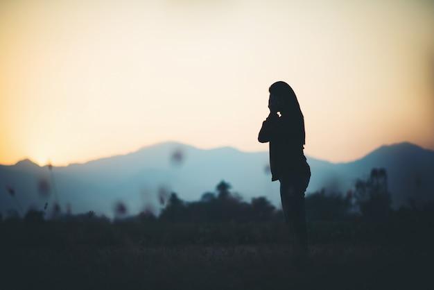 美しい空の背景を祈る女性のシルエット