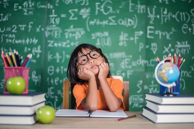 Задумчивая девочка с книгой возле школьной доски