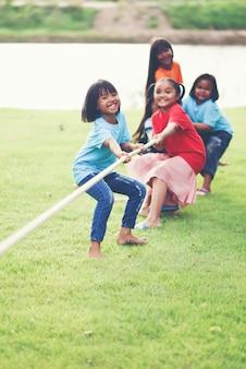 子供たちが公園で綱引きをしているグループ