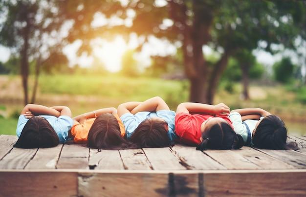 一緒に座っている子供の友達の腕のグループ