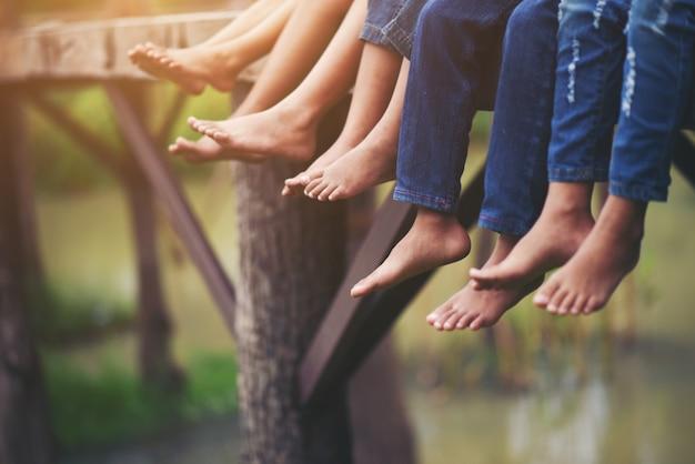 公園でリラックスして座っている子供たちの足