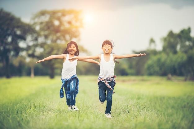 Две маленькие симпатичные девушки бегают по зеленой траве. лучшие друзья.