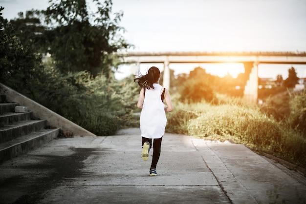 ハッピーランナーの女性は公園のジョギング運動で走ります。
