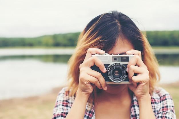 彼女のヴィンテージカメラを使用して、若い女性のクローズアップ