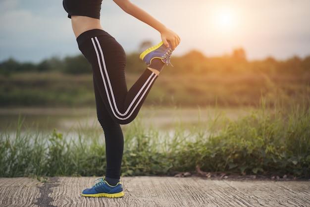 健康的な若い女性は、公園で訓練セッションの前に屋外で運動を温めています。