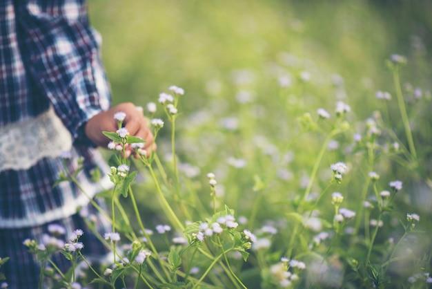 草原で野生の花に触れる少女の手を閉じます