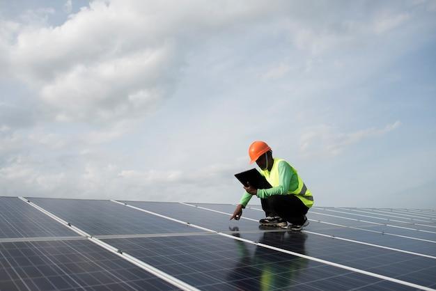 Техник-инженер проверяет обслуживание панелей солнечных батарей.