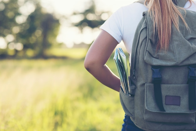 砂利道を歩くバックパックを持つハイキングの女性