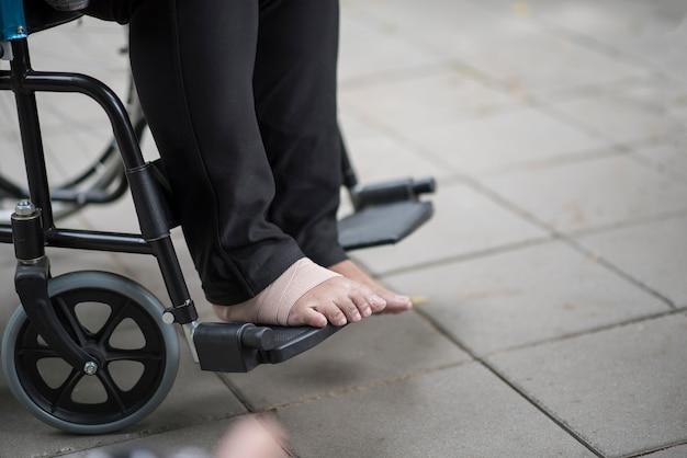 車椅子に座っている高齢者の足の痛みを閉じます