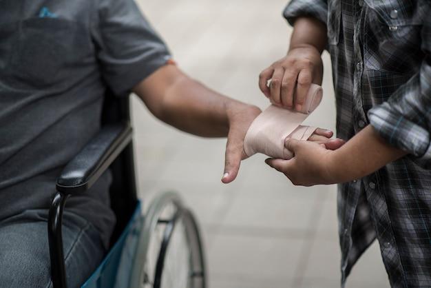 女性は包帯付きの車椅子患者に座っている男性に手を差し伸べている。
