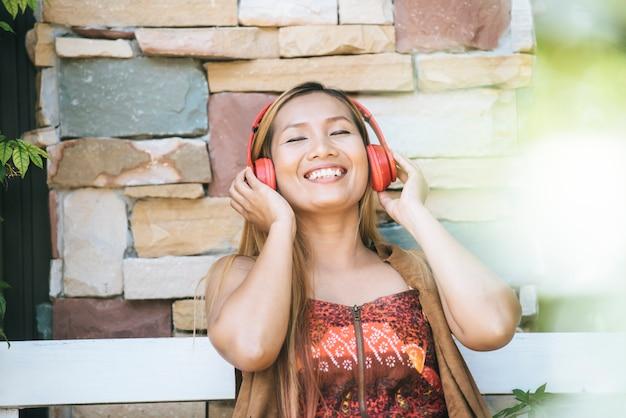 幸せな若い女性は、カフェでリスニング好きな音楽とリラックス