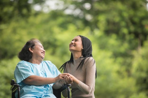 Внучка разговаривает с бабушкой, сидя на инвалидной коляске, жизнерадостная концепция, счастливая семья
