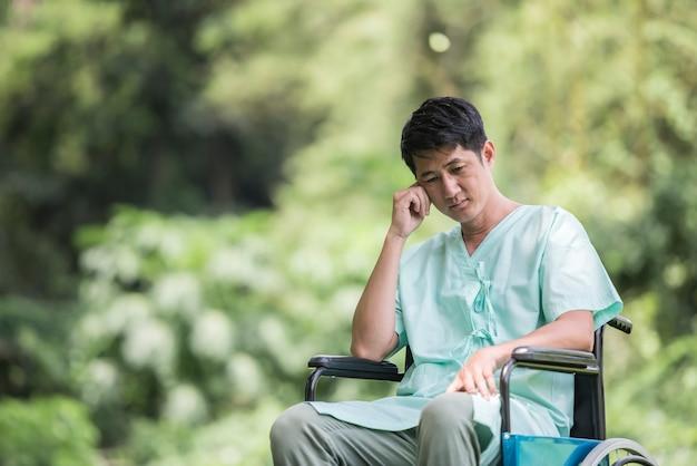 Один молодой инвалид в инвалидной коляске в саду