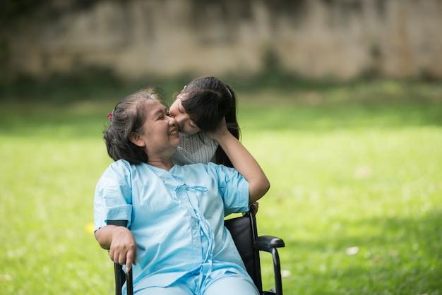 病院の庭の孫娘と車いすでの高齢祖母