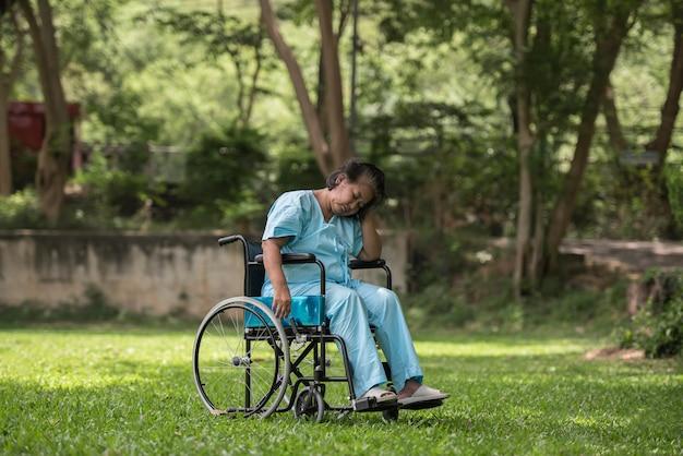 孤独な高齢者の女性は悲しい気持ちで車椅子の病院で庭に座って