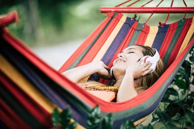音楽を聞くヘッドフォンで美しい幸せな若い女性