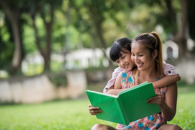 母と娘が公園の娘におとぎ話を読んでいる