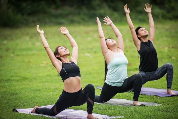 公園で健康的なヨガの行動運動