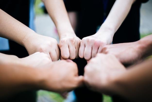拳のバンプジェスチャーを作る手を立てて学生のクローズアップ。