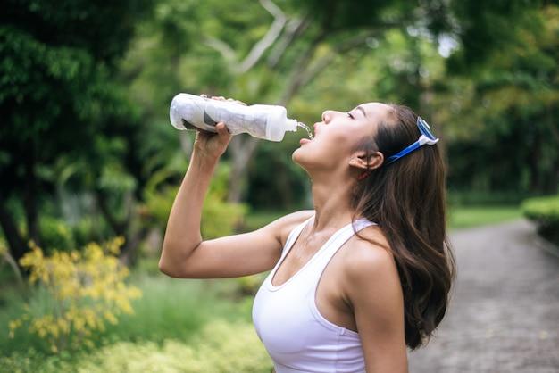 ジョギングの後、プラスチック製のボトルから若い健康的な女性の飲み水。