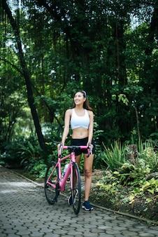 公園でピンクのバイクを持つ若い美しい女性の肖像画。魅力的な健康な女性。