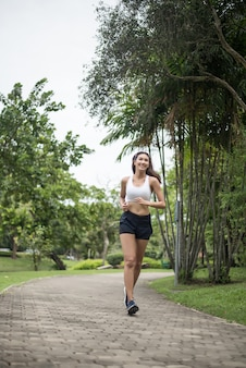 公園で走っている若い美しいスポーツの女性。健康とスポーツのコンセプト。