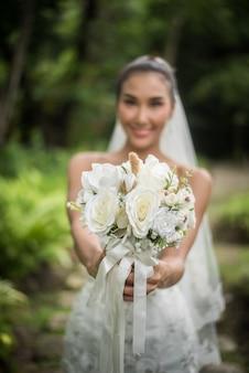 Красивая невеста с свадебным свадебным букетом.
