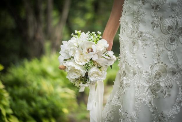 花嫁の手で結婚式のブライダルブーケのクローズアップ。