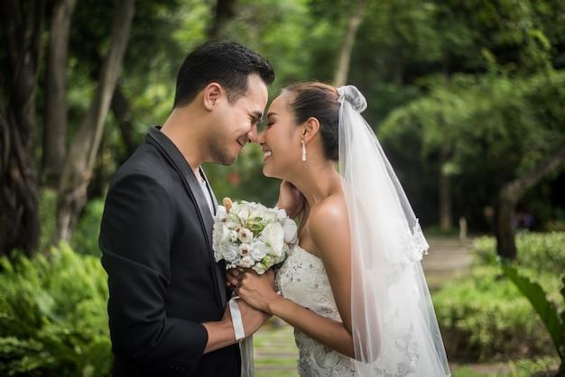 愛の結婚式の日の新郎新婦は彼の花嫁に花の花束を与える。