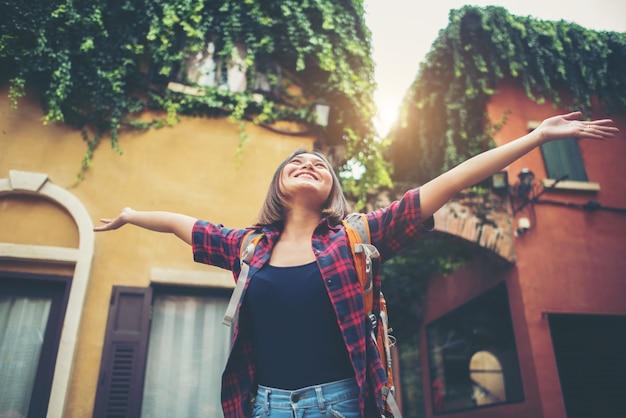 幸せな若い女性は都市で彼女の手を上げる旅行を楽しむ。女性のライフスタイルの概念。