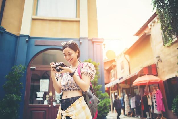 ヤングヒップスターの女性は、旅行中に都市で写真を撮って楽しむ。