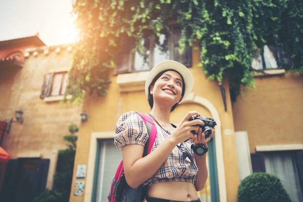 Портрет молодой хипстер женщина рюкзак путешествия фотографировать в городе.