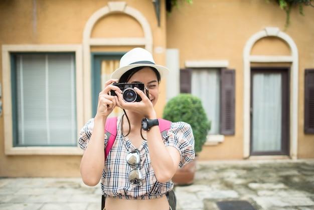 都市部で写真を撮って旅行する若いヒップスターの女性のバックパックを閉じます。